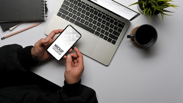 ノートパソコンのモックアップで作業中にスマートフォンを使用して男性の手の上面図