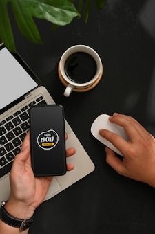 スマートフォンとラップトップで作業している男性の上面図