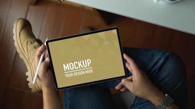Вид сверху на человека, использующего макет планшета с пустым экраном, сидя в офисной комнате