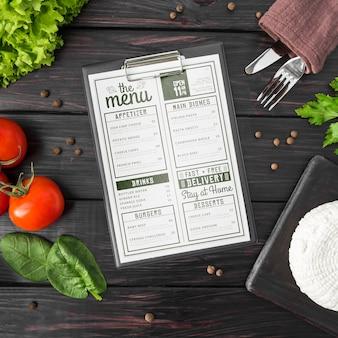 Вид сверху меню со столовыми приборами и помидорами