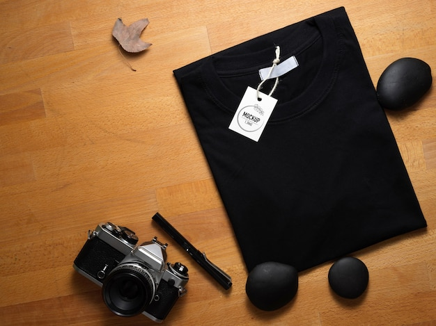 カメラ付き木製テーブルに値札が付いているモックアップ黒tシャツの上面図