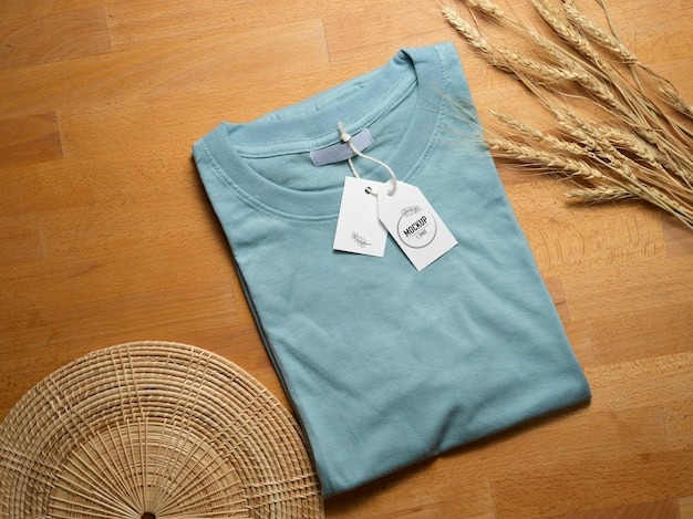 Вид сверху макета синей футболки с макетом ценника на деревянном столе с украшениями