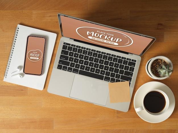 Вид сверху макета цифровых устройств с ноутбуком, смартфоном, кофейной чашкой, канцелярскими принадлежностями и аксессуарами