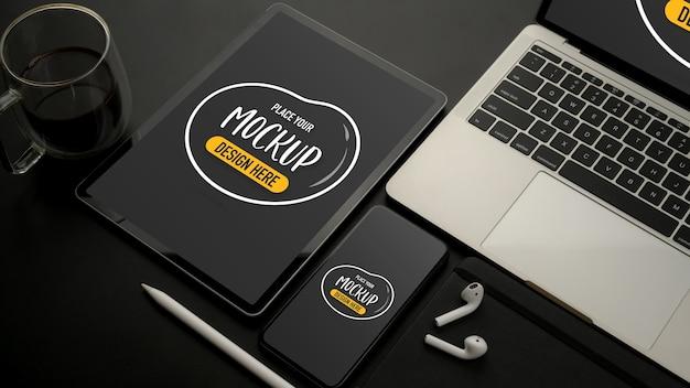 黒い机の上にタブレット、スマートフォン、ラップトップ、アクセサリーとモックアップデジタルデバイスの上面図