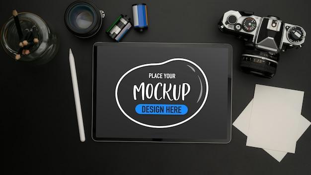 Вид сверху макета цифрового планшета на черном столе с камерой, блокнотом, объективом и канцелярскими принадлежностями