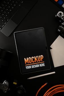 デジタルデバイスとカメラと黒いテーブルの上のモックアップデジタルタブレットの上面図