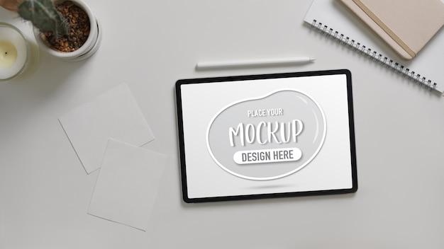 Вид сверху макета цифрового планшета на белом столе с ноутбуками