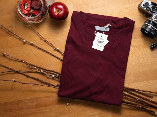 Вид сверху макета красной футболки с ценником на деревянном столе с украшениями
