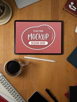 供給と文房具の木製の机の上のタブレットのモックアップのトップビュー