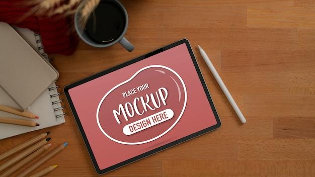 Вид сверху макета планшета на деревянном рабочем столе с копией пространства, цветными карандашами и канцелярскими принадлежностями