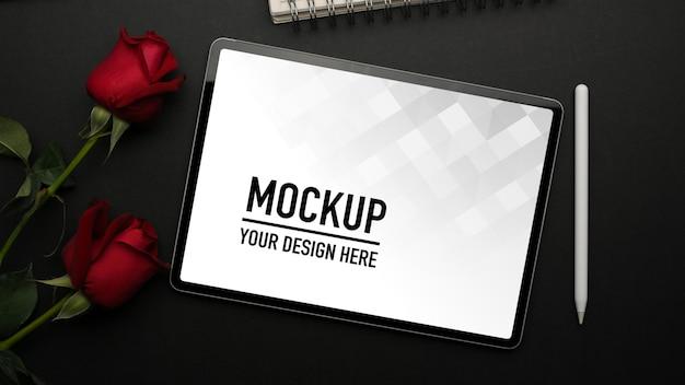 Вид сверху макета цифрового планшета на черном столе со стилусом