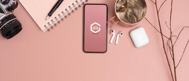 ピンクの研究テーブルのモックアップスマートフォンのトップビュー
