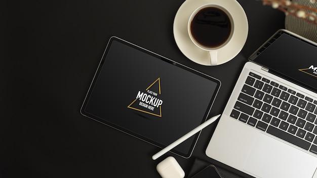 黒いテーブルにタブレットとラップトップコンピューターのモックアップを備えたモダンなワークスペースの平面図