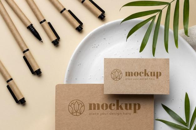 Вид сверху бумажных канцелярских принадлежностей на тарелке с листьями и карандашами