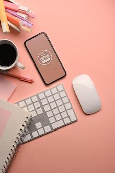 스마트 폰으로 분홍색 창의적인 작업 공간의 상위 뷰