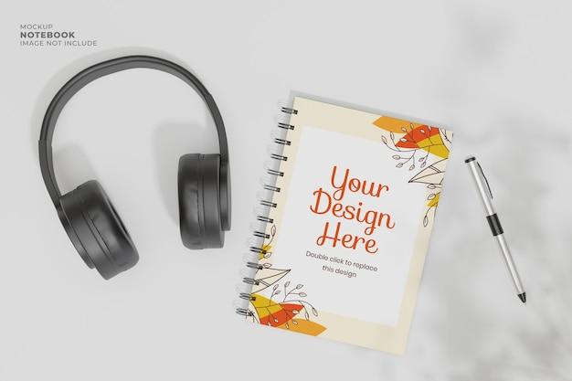 ヘッドフォンとペンのモックアップと机の上のリングノートブックの上面図