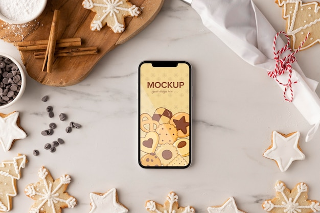 Вид сверху на макет смартфона со снежинками и корицей