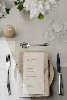 Вид сверху макета весеннего меню на тарелке со столовыми приборами и стаканами