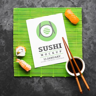 Вид сверху суши с палочками для еды и соевым соусом на бамбуковом валике