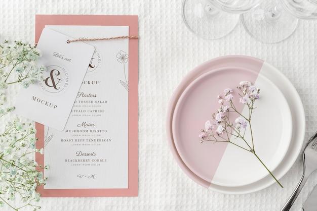 Расположение стола с макетом весеннего меню и тарелками, вид сверху