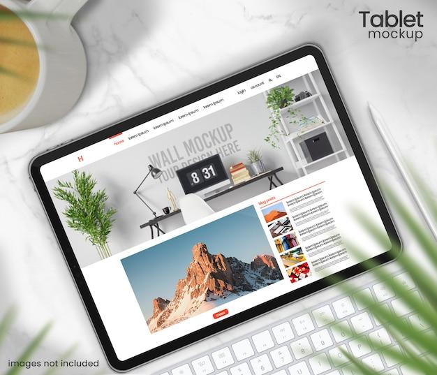 대리석 테이블에 스타일러스가있는 태블릿 모형의 윗면보기