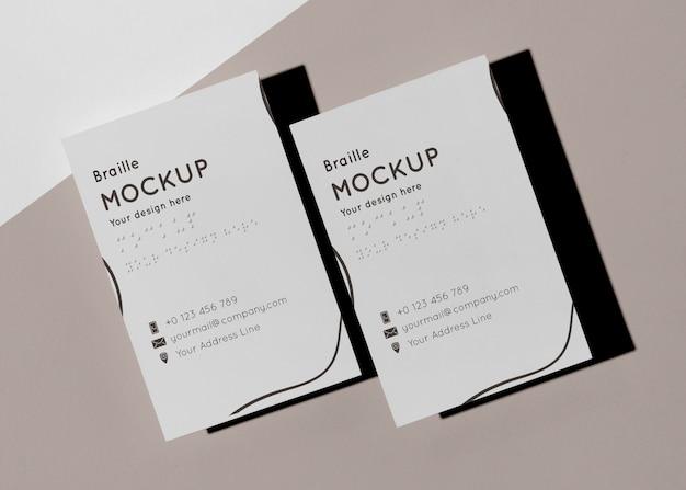 Вид сверху двух визиток с тисненым шрифтом брайля
