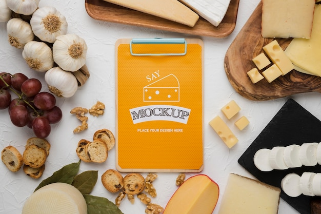 Вид сверху разнообразия сыра с блокнотом и чесноком
