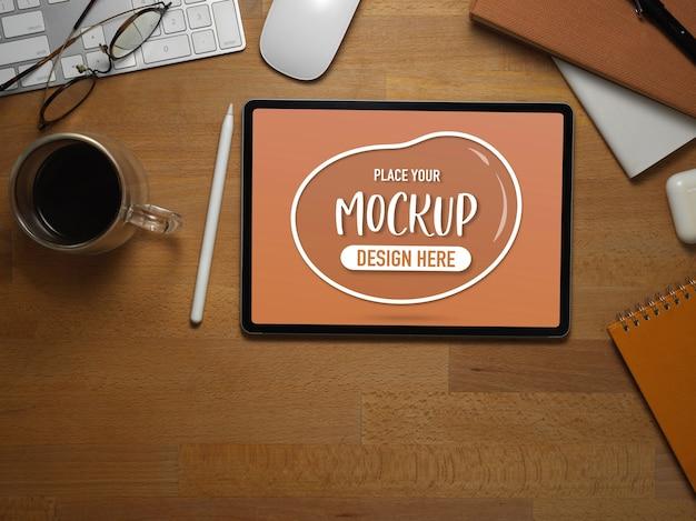 タブレットのモックアップ付き木製オフィスデスクのトップビュー
