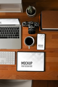 Вид сверху на деревянный стол с макетом планшета, ноутбука и смартфона