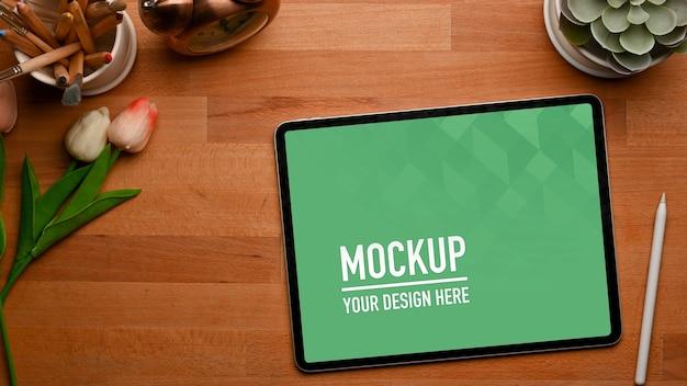 タブレットのモックアップ、スタイラス、装飾が施された木製テーブルの上面図