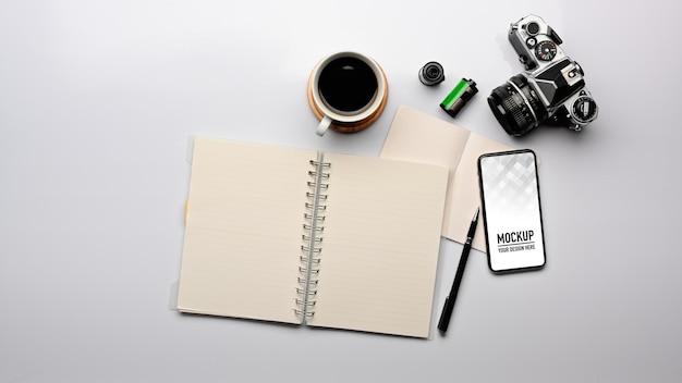 空白のノートブック、スマートフォンのモックアップとワークスペースの上面図