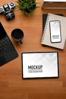 Вид сверху на рабочее пространство с макетом цифрового планшета и смартфона