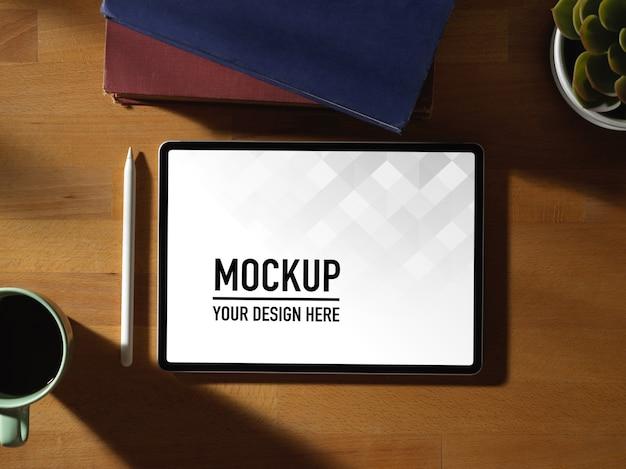 디지털 태블릿 모형, 스타일러스, 책 및 커피 컵이있는 작업 공간의 상위 뷰