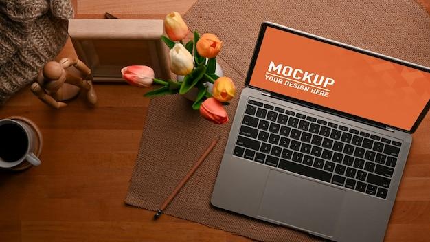 Вид сверху на рабочее пространство с макетом ноутбука и украшениями