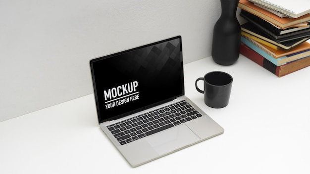 ノートパソコンのモックアップとマグカップとワークスペースの上面図