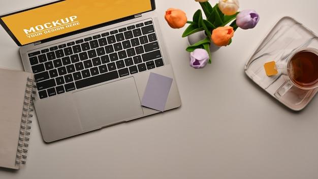 Вид сверху на рабочее место с макетом ноутбука, вазой для цветов и чашкой чая на столе