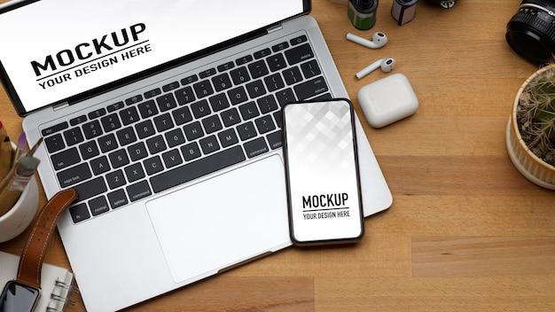 ノートパソコン、スマートフォン、木製のテーブルの上の消耗品とワークスペースの上面図