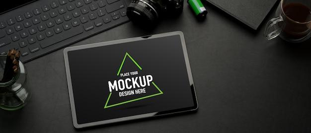 モックアップタブレット、キーボード、カメラ、消耗品、黒いテーブルのコピースペースとワークスペースの上面図