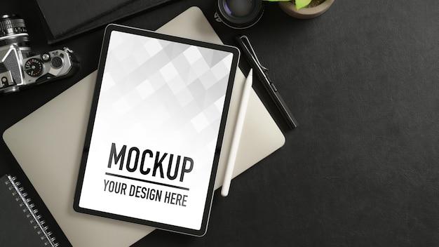 Вид сверху на рабочее пространство с макетом планшета, ноутбука, расходных материалов и копией пространства на черном столе