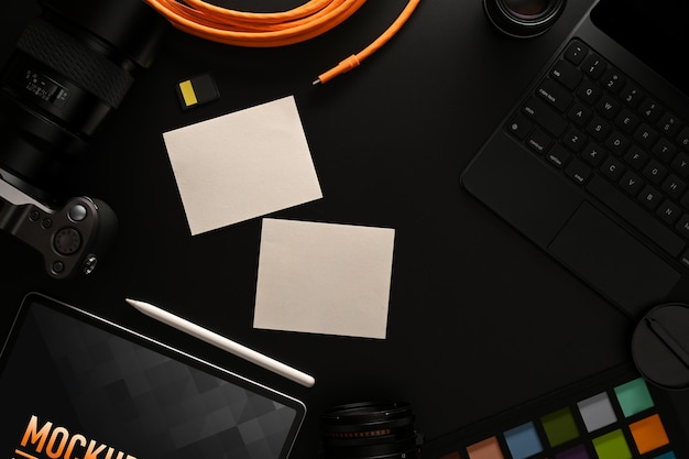 Вид сверху на рабочее пространство с блокнотом, макетом планшета и цифровыми принадлежностями на черном столе