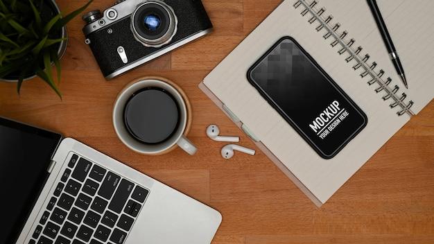 Вид сверху на рабочее пространство с макетом смартфона и канцелярскими принадлежностями