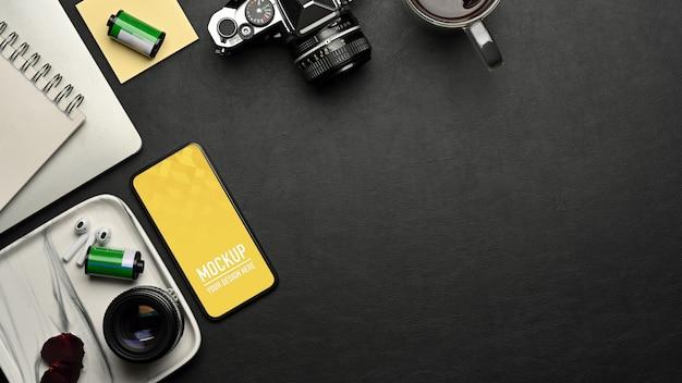 Вид сверху на рабочее пространство с макетом смартфона, камерой и принадлежностями