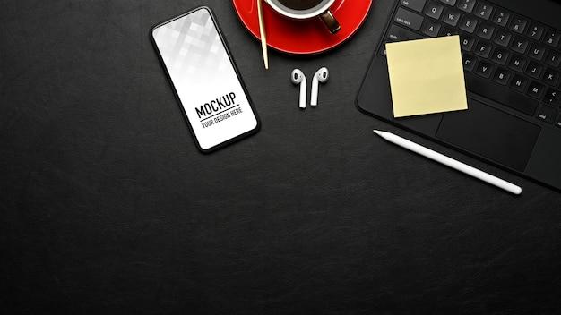 Вид сверху на рабочее пространство с макетом смартфона, клавиатурой и аксессуарами