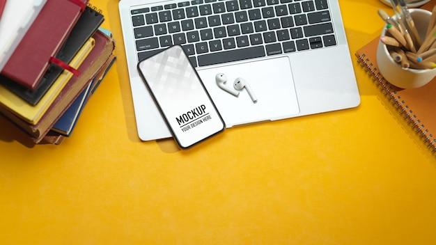 Вид сверху на рабочее пространство с макетом смартфона, ноутбуком, наушниками