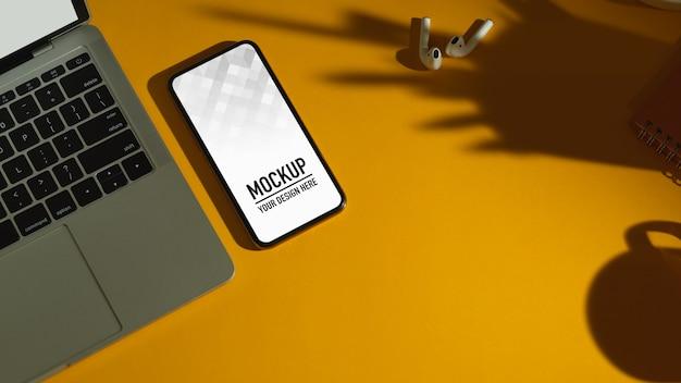 Вид сверху рабочей области с макетом смартфона, ноутбук на желтом столе