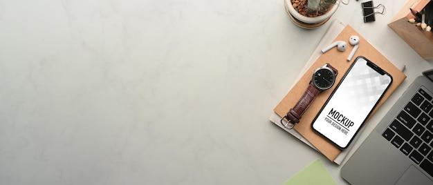 Вид сверху на рабочее пространство с макетом смартфона