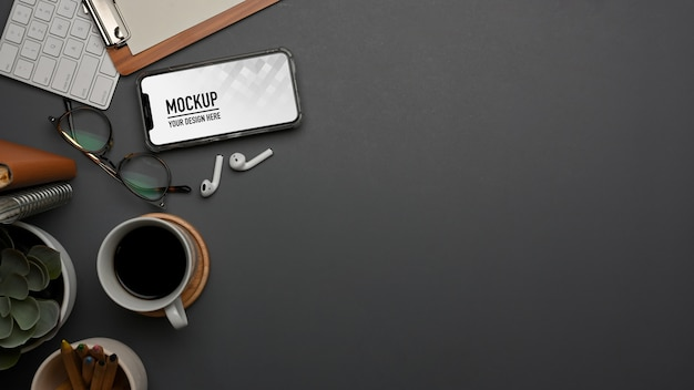 Вид сверху на рабочее пространство с расходными материалами и макет смартфона
