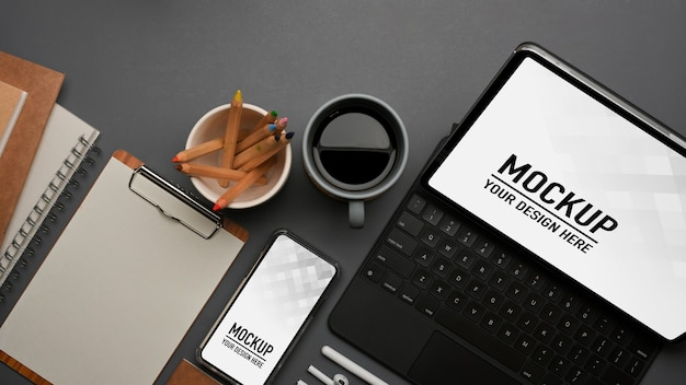 Вид сверху на рабочее пространство с клавиатурой планшета и макетом смартфона