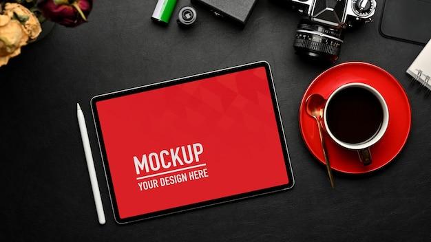 Вид сверху на рабочее пространство с макетом планшета, камерой и принадлежностями на черном столе