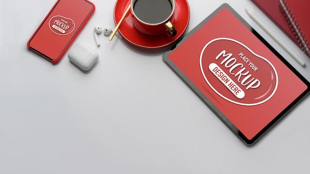 モックアップタブレット、スマートフォン、コーヒーカップ、イヤホン、コピースペースを備えた作業台の上面図